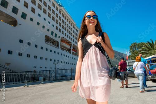 Leinwandbild Motiv Woman tourist near the big cruise liner