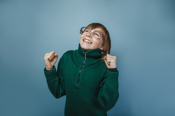 European-looking boy of ten years in glasses on gray background