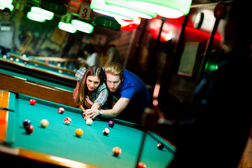 Young couple playing pool