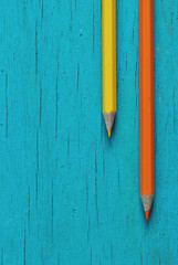 yellow and orange pencils on blue wooden background