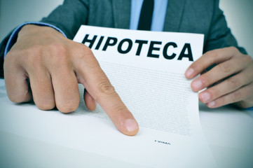 man with a document with the word hipoteca, mortgage loan contra