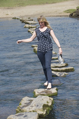 Woman in barefeet crossing a river using stepping stones