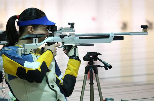 Leinwanddruck Bild woman aiming a pneumatic air rifle