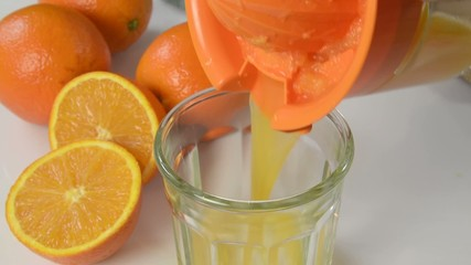 Pouring fresh squeezed orange juice into a glass