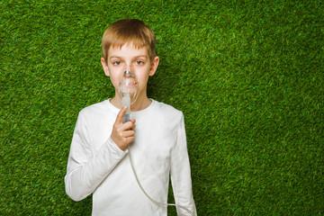 Boy in white breathing through inhalator mask