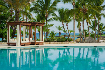 Swimming Pool at tropical beach - summer vacation background.