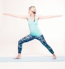 Active Blond Woman in Virabhadrasana II Yoga Pose