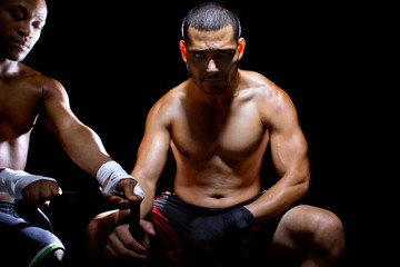 Latin MMA fighter or Boxer with trainer applying athletic tape