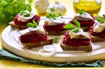 Canape from rye bread with herring slice and beetroot.