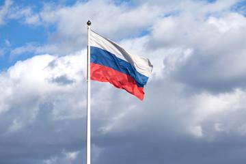 Russian flag on the flagpole waving on cloudy sky