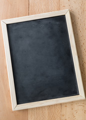 Closeup of vertical empty blackboard with wooden frame
