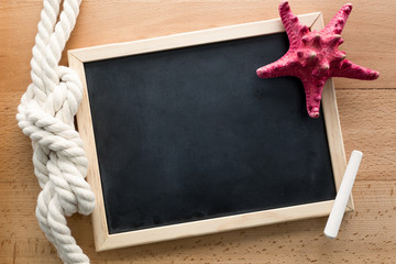 Horizontal shot of clean blackboard decorated by marine knot