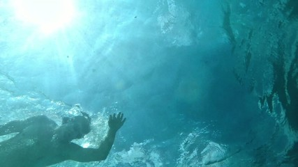 Slow motion as man swims underwater on surface of sea abov