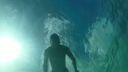 Low angle man swimming on surface of sea backlit by sun