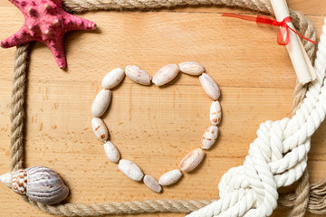 Heart made of seashells with border of ropes and knots on boards