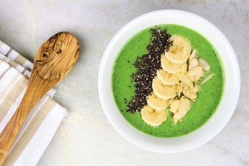 Green smoothie bowl with chia seeds, bananas and almonds