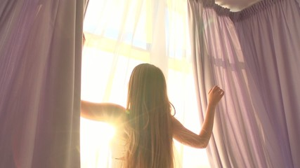 Girl opens curtains on big window and let the light in the room