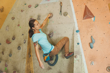 Woman climbing artificial boulder indoors
