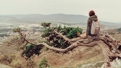 Traveler woman sitting on a tree