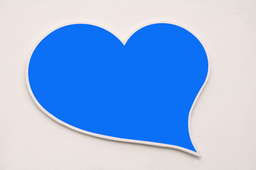 Blue heart shape on white wall background