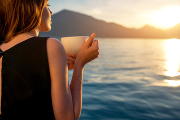 Young woman drinking coffee on the pier at sunrise