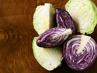 two varieties of cabbage (green and red) on a wooden table