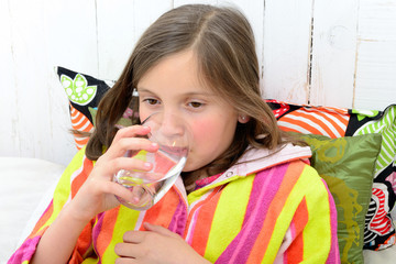 a sick girl drinking a glass of water