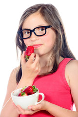 a little girl eating a strawberry