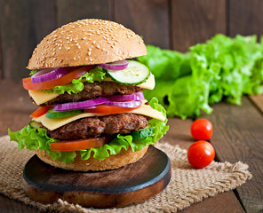 Big juicy hamburger with vegetables and beef on a wooden table