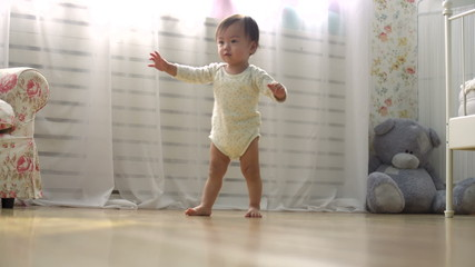 one year a small asian baby taking its first steps,dolly shot