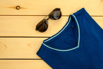 Blue t-shirt with sunglasses on wooden board