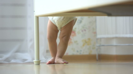 one year a small asian baby taking its first steps,close up