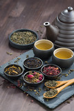 assortment of fragrant dried teas and green tea on wooden table