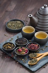 assortment of fragrant dried teas and green tea on wooden table © cook_inspire