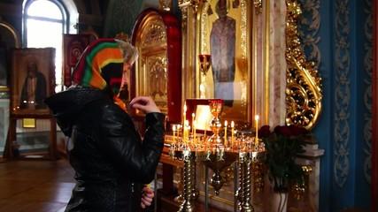 Женщина, девушка зажигает, ставит свечи и крестится в церкви.