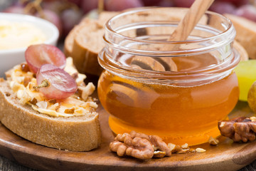 flavored honey, bread with butter and grapes, close-up