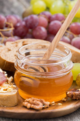 flavored honey, bread with butter and grapes, vertical, close-up