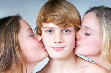 Zwei Mädchen küssen Jungen auf Backe
