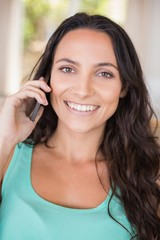 Pretty brunette calling with her mobile phone