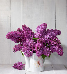 Lilac Bouquet in ceramic jug against a old wooden wall.