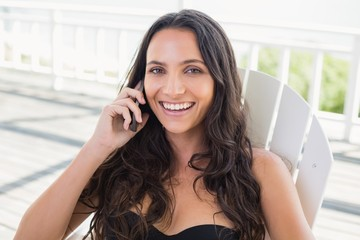 brunette sitting on a chair and calling with her mobile phone