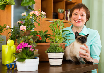 Woman with cat and flower plants