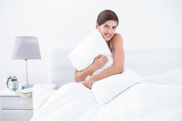 Happy brunette hugging her pillow