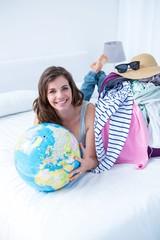 Smiling brunette lying on bed holding her globe