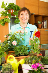 Smiling mature woman caring for plants