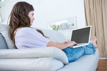 Pretty brunette using her laptop on couch