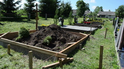 Freshly made grave soil and foundation in cemetery