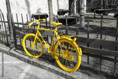 Leinwandbild Motiv Yellow bicycle on the gray background