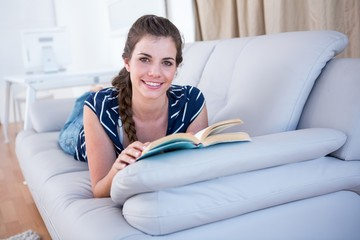 Happy brunette reading a book