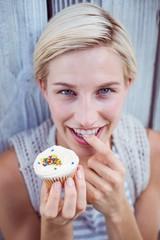 Pretty blonde woman tasting the cupcake